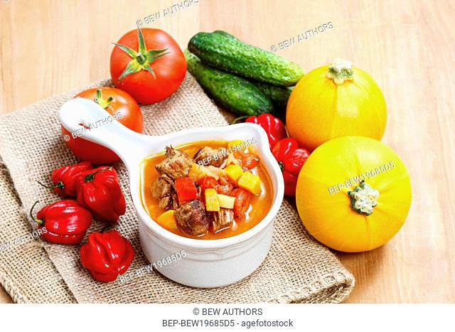Bowl of goulash soup and fresh vegetables on wooden table