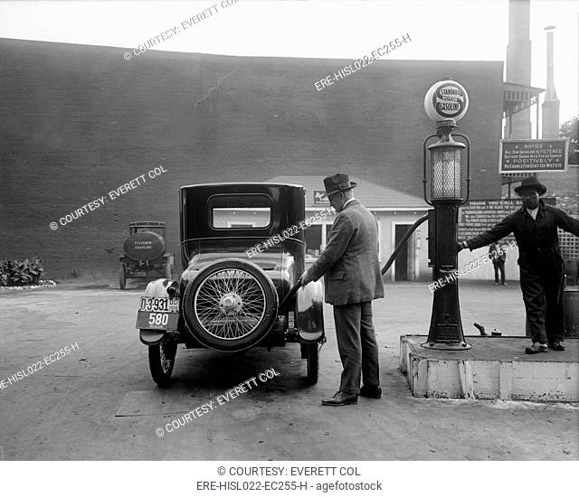 Man fueling his car at a self-service Standard Motor gas station in Washington D.C. area. A sign tells customers the gasoline is filter and contains no dirt or...