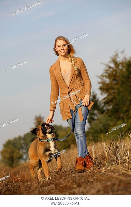 Woman walking with dog in landscape having fun