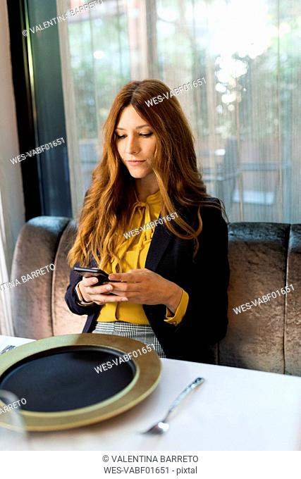 Woman sitting at table in a restaurant using cell phone