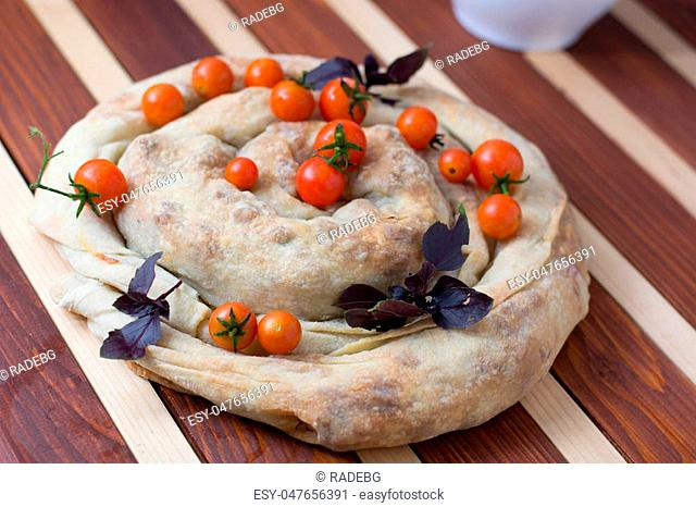 spiral filo pie burek with cherry tomatoes on wooden table