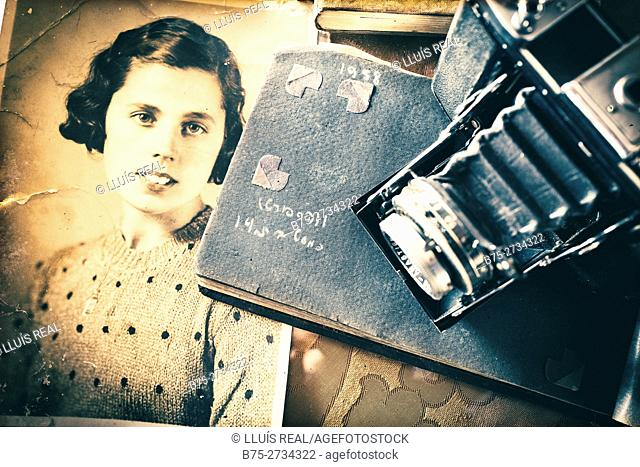 Old black and white portrait of woman with photo album and vintage camera