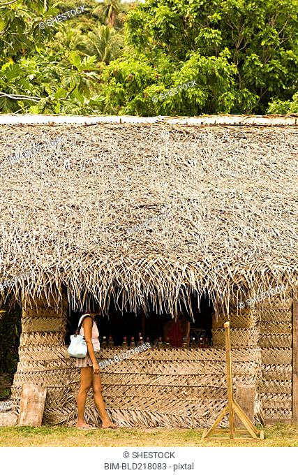 Woman standing under thatched hut roof