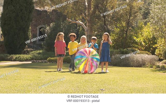 Slow motion of five children pushing beach ball towards camera in park