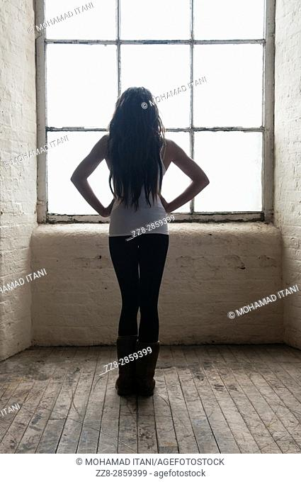 young woman standing near the window