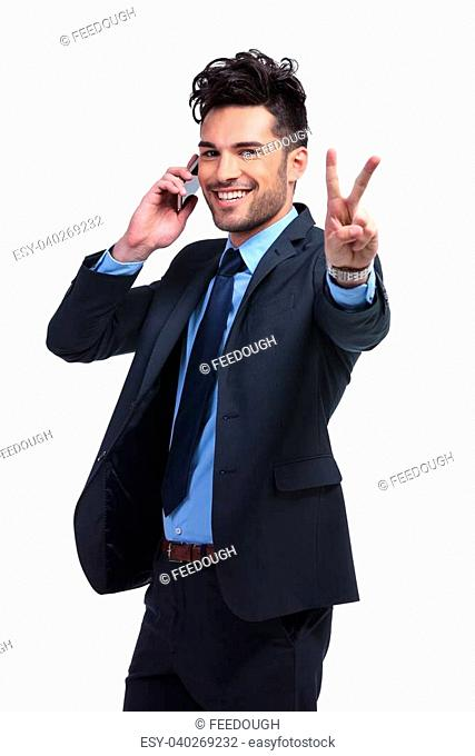 young business man talking on the phone and making the victory hand gesture