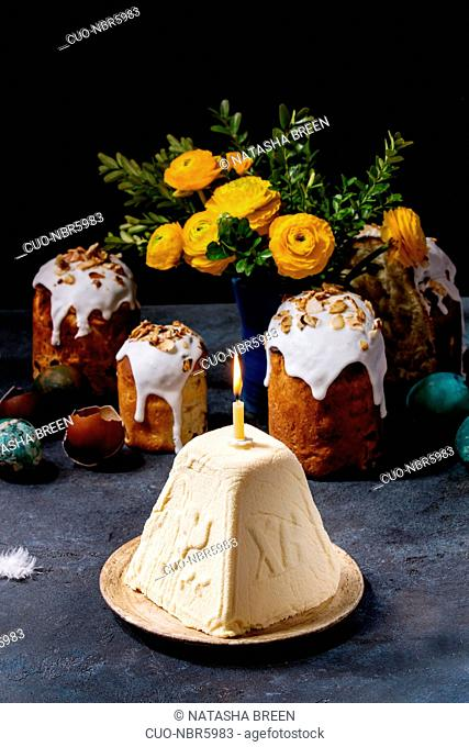 Traditional Russian Easter cottage cheese dessert, Orthodox Paskha with burning candle standing in ceramic plate on dark texture table with kulich cakes