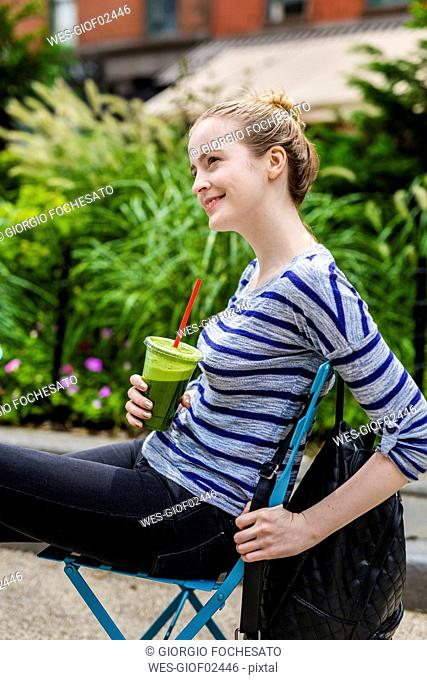 Smiling young woman having a break drinking a smoothie outdoors
