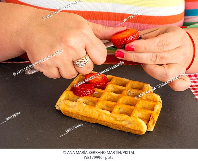 A woman with red fingernails cutting a strawberry and placing it on a Belgian waffle