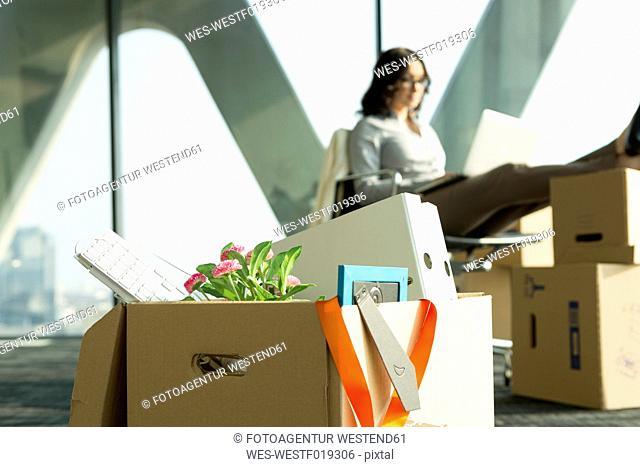 Cardboard box on office floor with businesswoman in background