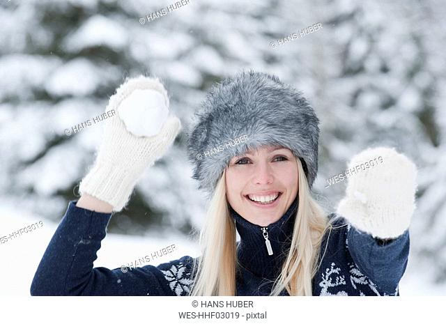 Austria, Salzburger Land, Altenmarkt, Zauchensee, Young woman throwing snowball, smiling, portrait, close-up