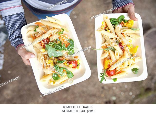 Girl holding two plates of pasta salad during a picnic in forest