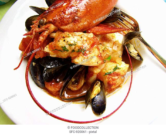 Lobster and mussel stew on plate with fork