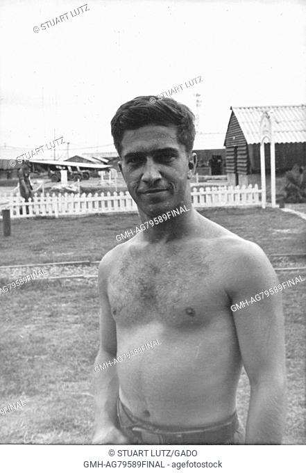 A candid photograph of a United States Army serviceman from the waist up without a shirt on, he is smiling for the photographer