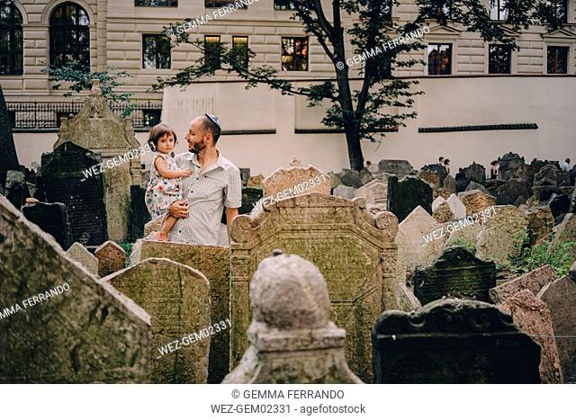 Czechia, Prague, father and baby girl visiting the old Jewish Graveyard