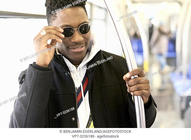 young man touching sunglasses in tram, public transport, in Munich, Germany
