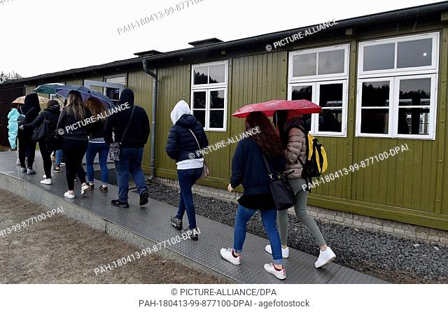 13 April 2018, Germany, Oranienburg: Agroup of visitors going into the barracks 38 at the former concentration camp where Jewish inmates were murdered