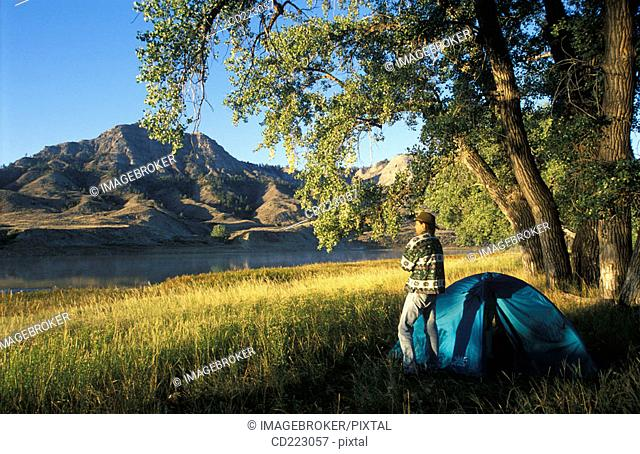 Campsite on the river with a man shivering in a cold morning, Missouri River, Missouri Breaks National Monument, Blaine County, Northern Montana, USA