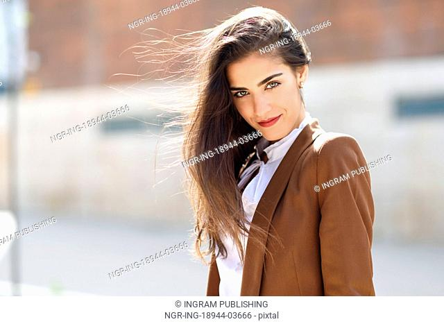 Young woman with nice hair in the wind standing in urban background. Businesswoman wearing formal wear with wavy hairstyle