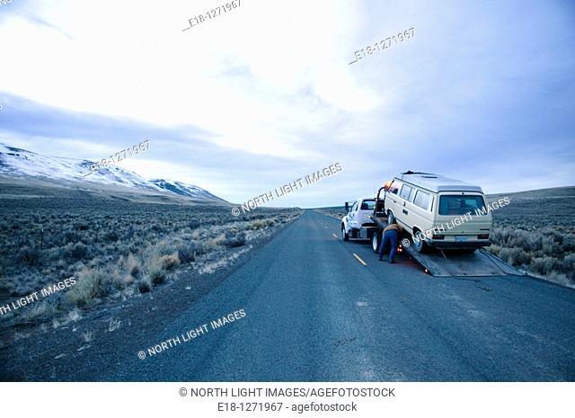 USA, Oregon, Fields.  Broken down 1980's VW Westfalia van loaded onto flatbed truck on lonely road in the desert