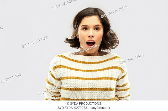 surprised young woman in striped pullover