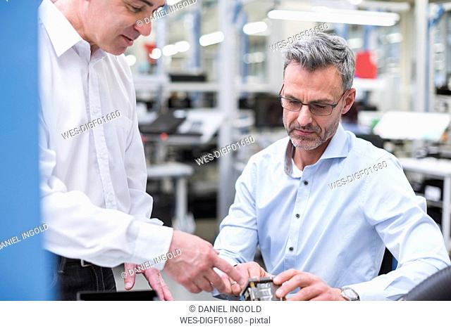 Two managers discussing product in company