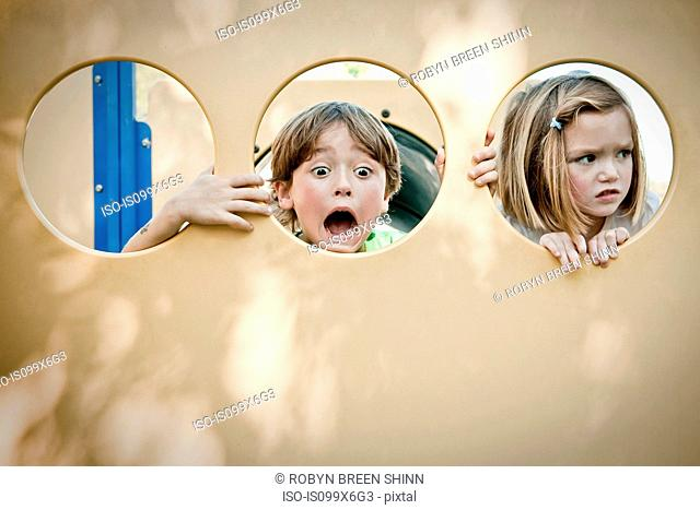 Boy and girl making faces through circles