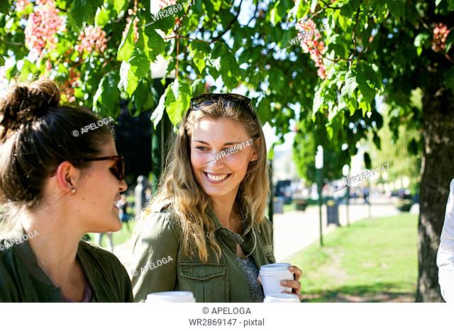 Happy woman looking at friend while holding disposable cups at park