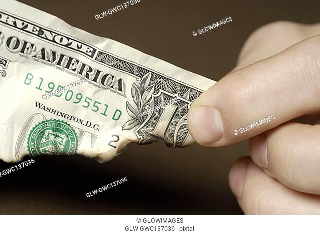 Close-up of a person's fingers holding a burnt American dollar bill