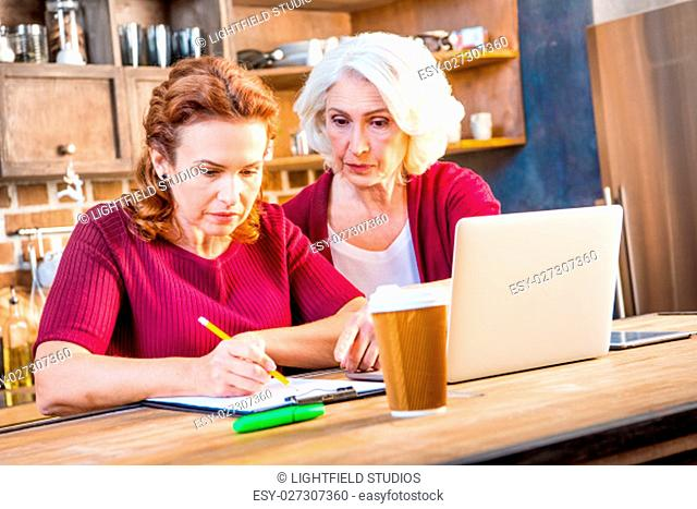 Mother and her adult daughter usind laptop and making notes sitting at table in kitchen