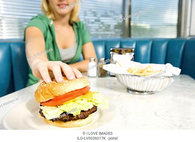 Teenage girl reaching for a hamburger in a diner