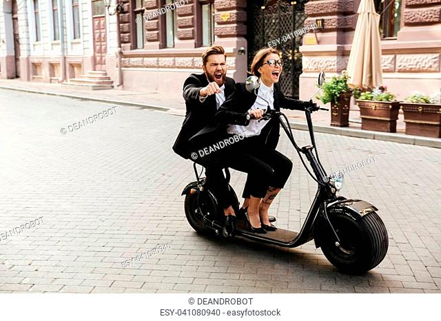 Excited young couple wearing smart clothes riding motor bicycle on a city street