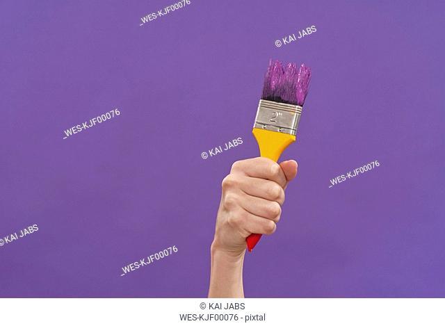 Hand holding paint brush, close-up