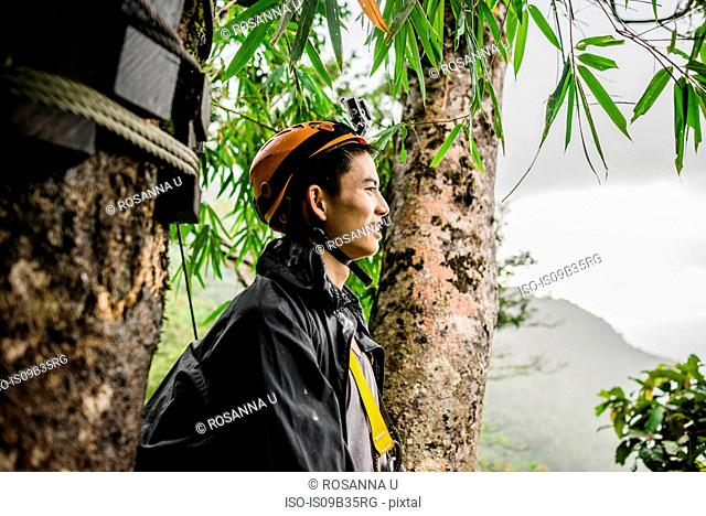 Young man by tree wearing climbing helmet looking away, Ban Nongluang, Champassak province, Paksong, Laos