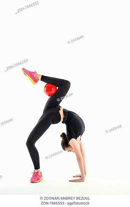 Rhythmic gymnast in a beautiful sportswear doing exercise with ball in studio