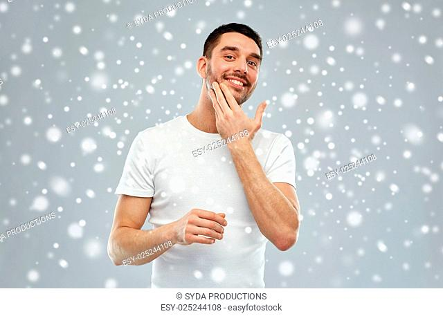 beauty, skin care, winter, christmas and people concept - smiling young man applying cream or lotion to face over snow on gray background