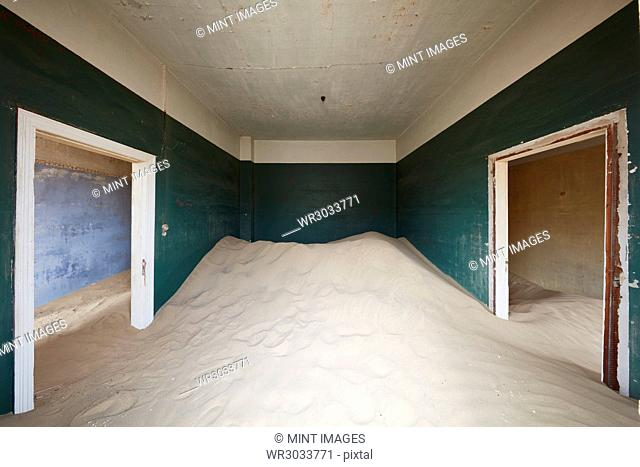 A deserted building, a room with painted walls and two doorways, and a heap of sand engulfing half the room
