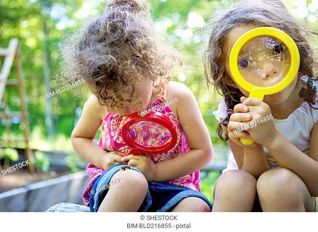 Girls examining caterpillar with magnifying glass