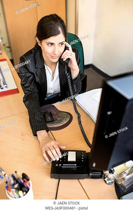 Woman on the phone at desk in office