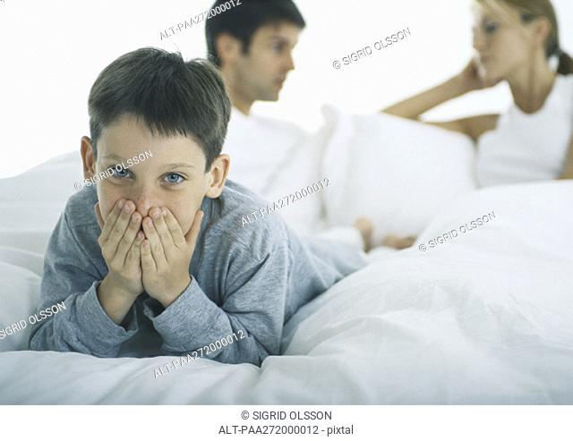 Boy lying on stomach in bed covering mouth with hands, parents discussing in background