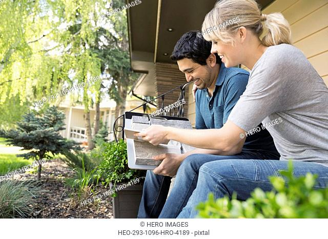Couple looking at granite swatches on front stoop