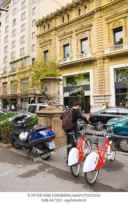 Man taking out a Bicing free bicycle in Gracia district of Barcelona Spain Europe