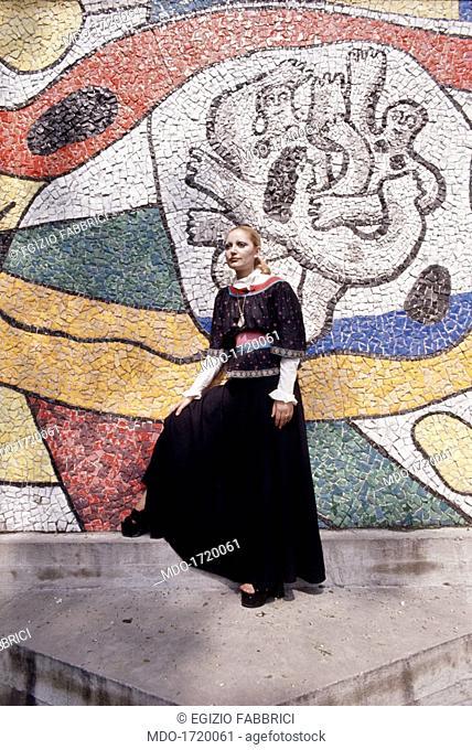 Mia Martini near a mural painting. Italian singer Mia Martini (Domenica Rita Adriana Berté) posing beside a polychrome mural mosaic. 1972