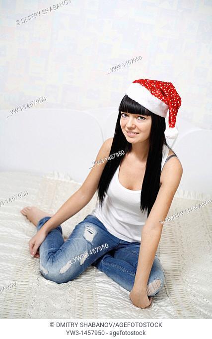 pretty brunette girl in Santa hat indoors