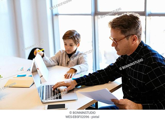 Businessman using laptop at desk in office with son sitting next to him