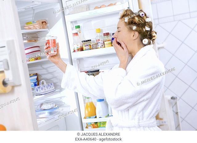 Young woman holding yogurt by refrigerator
