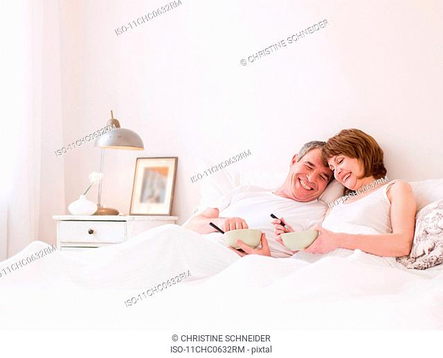 Eldery couple eating in bed