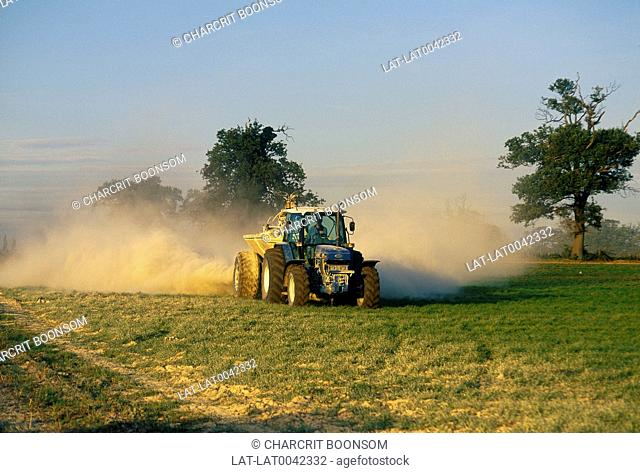 Tractor with lime sprayer. Spray. Trees. Field