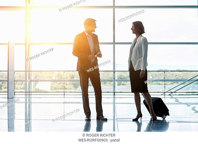 Businessman and businesswoman talking at the airport in backlight
