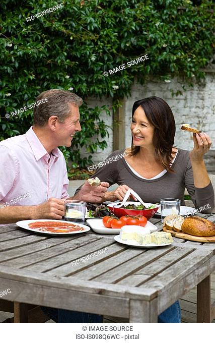 Mature woman and senior man dining al fresco